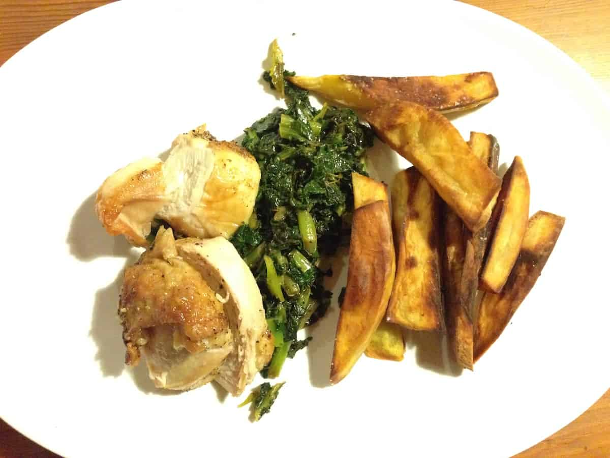 Roasted bone-in chicken breast, braised greens and onions, and baked sweet potato wedges